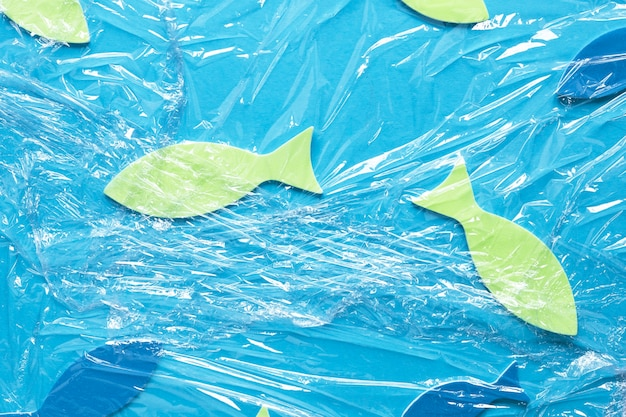 Flat lay of paper fish under plastic wrap
