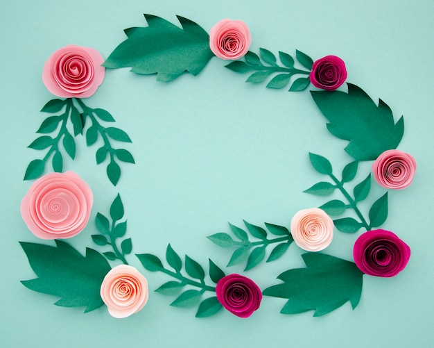 Flat lay paper flowers and leaves on blue background