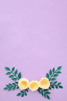 Flat lay paper flowers and leaves on purple background