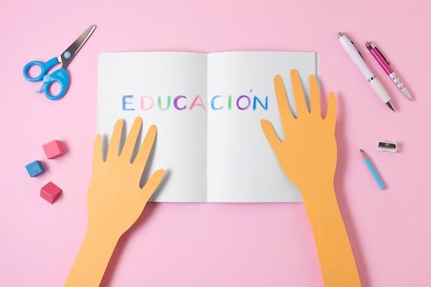 Плоские лежат бумажные руки с открытой записной книжкой