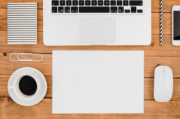 Flat lay paper mockup next to laptop