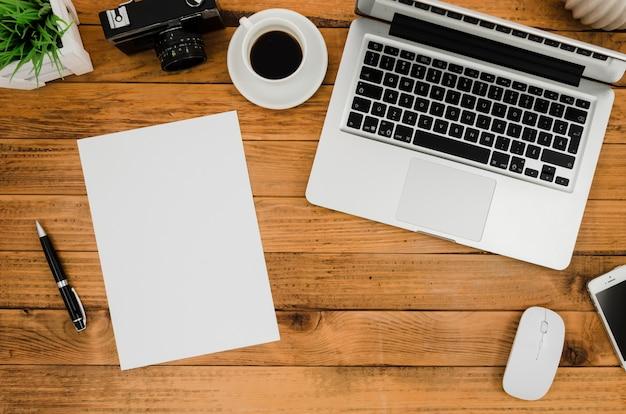 ノートパソコンの横にあるフラットレイ紙モックアップ