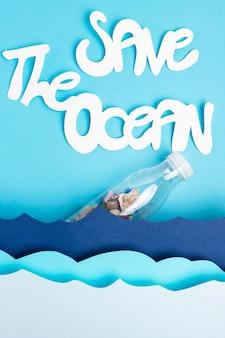 La disposizione piana delle onde dell'oceano di carta con la bottiglia di plastica e salva l'oceano