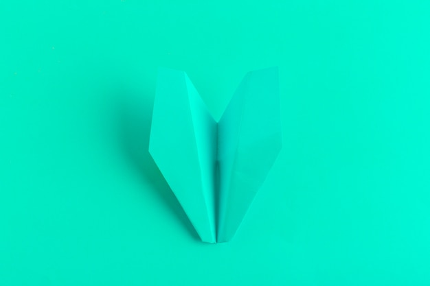 Flat lay of a paper plane on green pastel color background