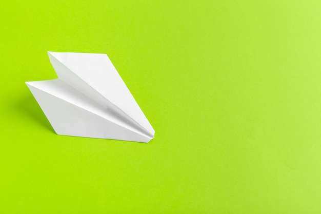 Flat lay of a paper plane on green pastel color