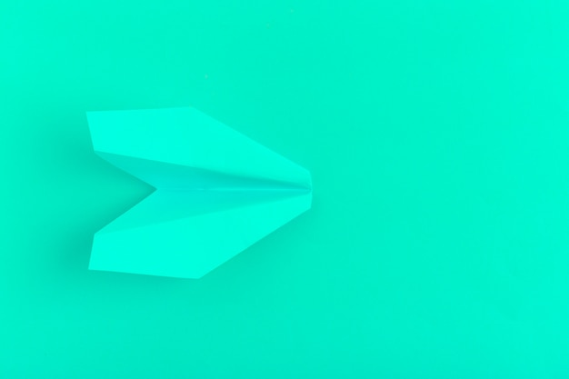 Flat lay of a paper plane on green pastel