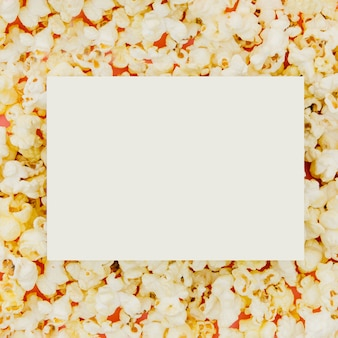 Flat lay of paper on popcorn for cinema concept