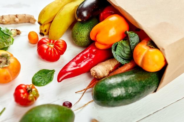 Плоская бумажная хозяйственная сумка с ассортиментом свежих овощей и фруктов, био-здоровыми, органическими продуктами на белой стене, стилем супермаркета, продуктовым магазином, диетической вегетарианской едой.