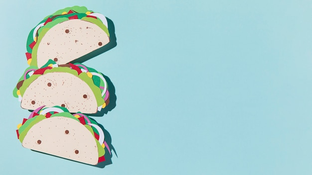 Flat lay paper tacos on blue background