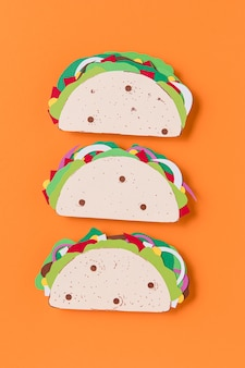 Flat lay paper tacos on orange background
