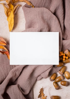 Flat lay of paper with autumn leaves and acorns
