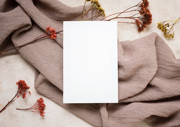 Flat lay of paper with autumn plant and fabric