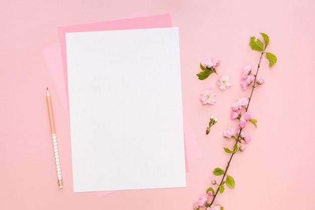 Flat lay of paper with flowers and pencil