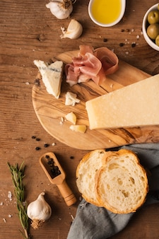 Flat lay parmesan prosciutto and bread on cutting board