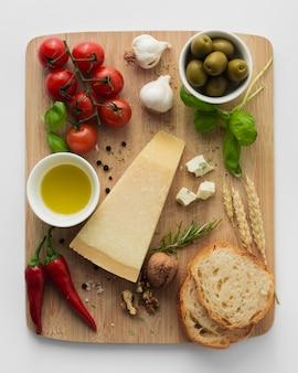 まな板の上のパルメザンチーズトマトとニンニクを平らに置く