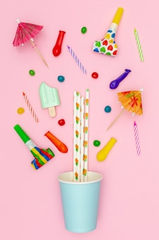 Flat lay party decorations on pink background
