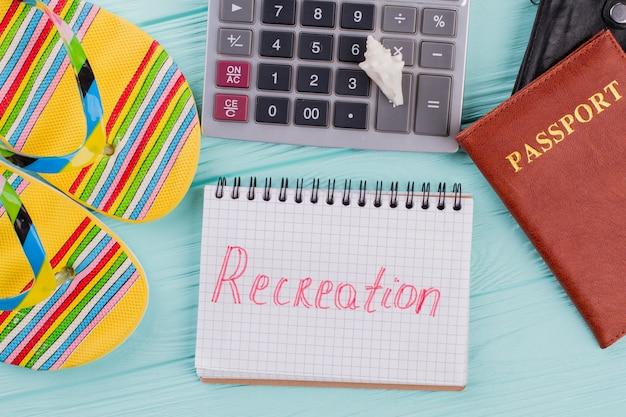 평평한 여권, 슬리퍼, 테이블 위의 계산기는 여행 계획을 의미합니다. 청록색 배경에 레크리에이션 단어가 있는 메모장.