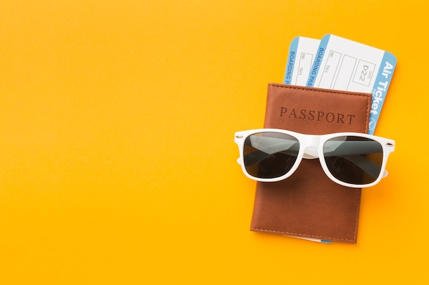 Flat lay of passport with sunglasses and plane tickets
