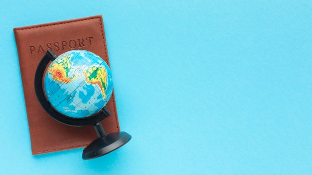 Flat lay passport and world globe