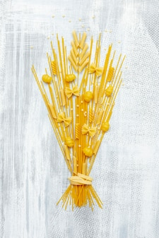 Flat lay of pasta bouquet on wooden background
