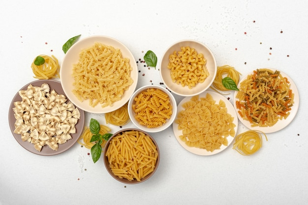 Flat lay of pasta in bowls on plain background