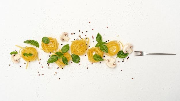 Flat lay of pasta mushrooms and basil on plain background