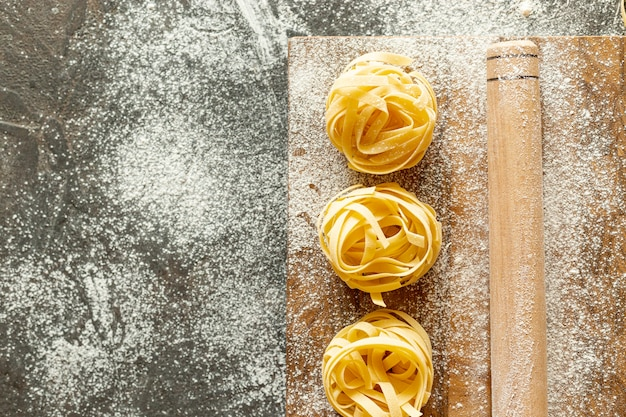 Flat lay of pasta and rolling pin with copy space