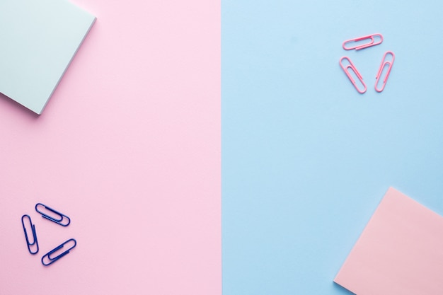 Flat lay on a pastel pink and blue background with a notepad paperclip