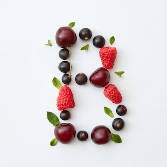 Flat lay pattern of letter b english alphabet from natural ripe berries - black currant, cherries