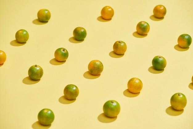 カラフルな背景に新鮮なカラマンシーまたは柑橘類のマイクロカルパのフラット レイアウト パターン。