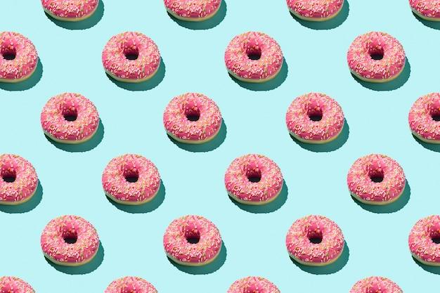 Плоский узор из вкусных розовых красочных пончиков на синем фоне.