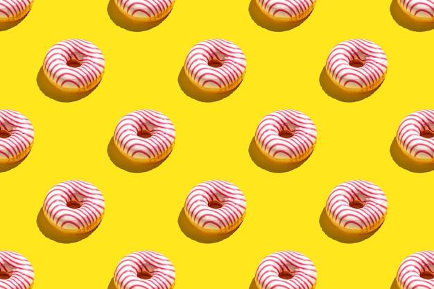 Плоский узор из вкусных розовых пончиков на желтом фоне.