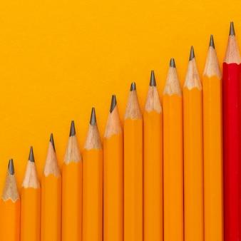 オレンジ色の背景にフラットレイ鉛筆