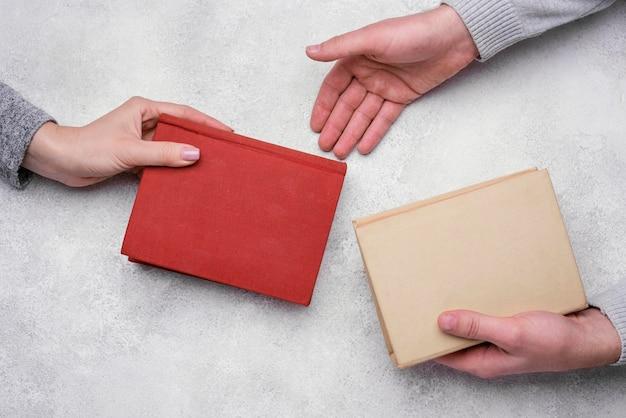 Flat lay of people exchanging hardback books