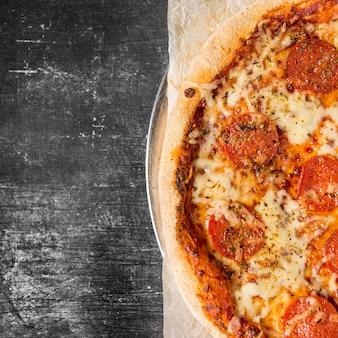 Pizza ai peperoni piatto laici sul vassoio