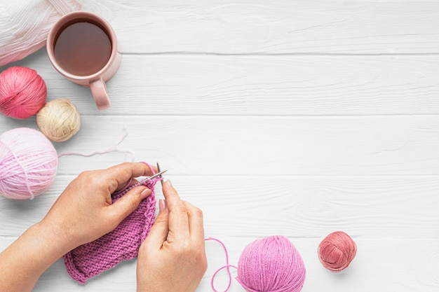 Flat lay of person knitting with yarn and copy space