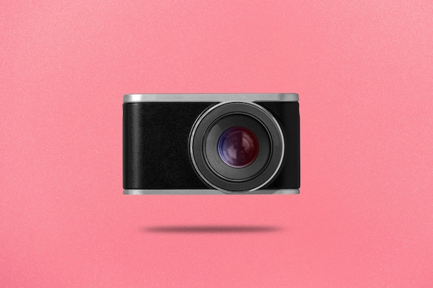 Flat lay photo of digital camera on pink background