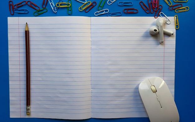 マウス、鉛筆、ペーパークリップ、青い木製の卓上にイヤホンと空白の開いたノートブックと学校の机のフラットレイ写真