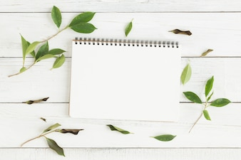 Flat lay photo of blank white notebook and green leaf on white wood table
