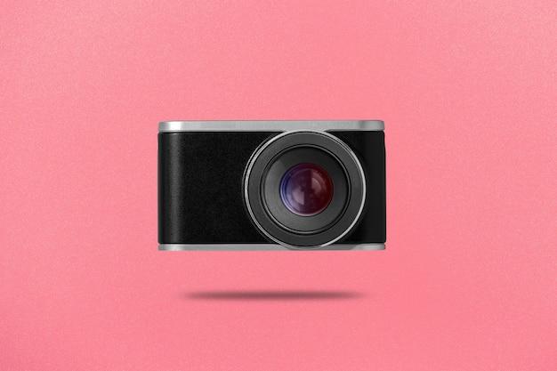 ピンクの背景にデジタルカメラのフラットレイ写真