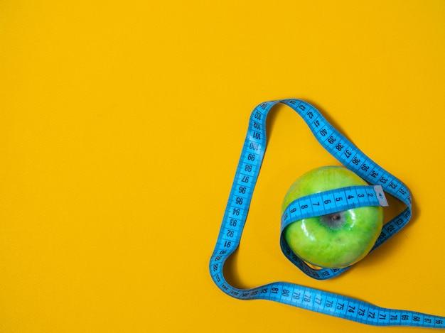 フラットは、フィットネスの概念の写真を置きます。青リンゴは健康的な栄養の概念