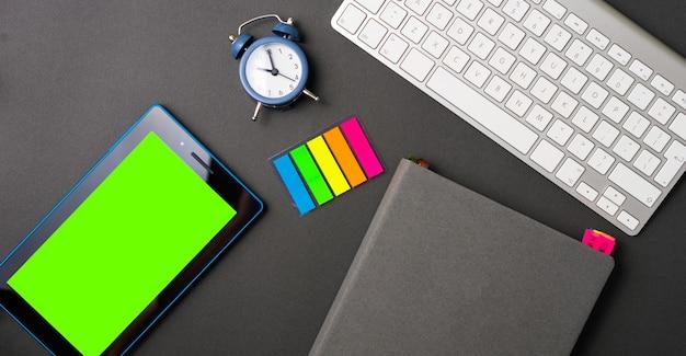 時計のタブレットとラップトップとカラフルなステッカーの議題を備えたオフィスデスクのフラットレイ写真