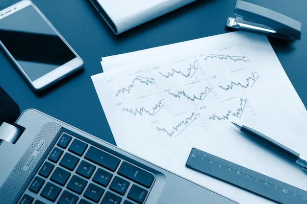 Плоская фотография рабочего стола с ручкой, ноутбуком и диаграммной бумагой