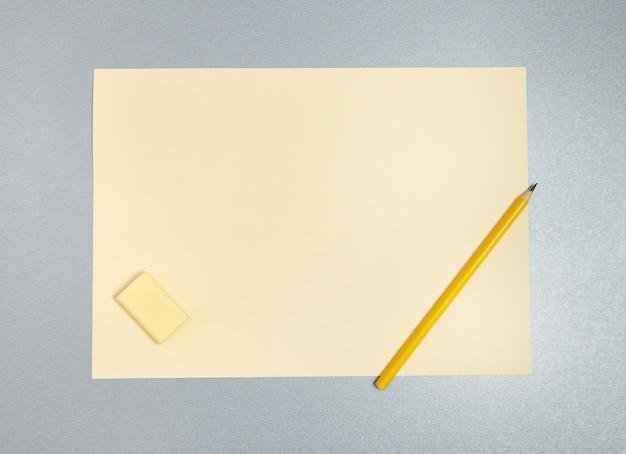 Плоская фотография желтого ластика, карандаша и листа бумаги на сером фоне