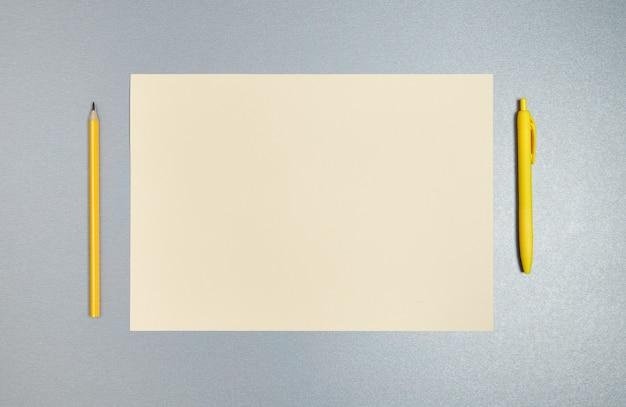 Плоская фотография желтой ручки, карандаша и листа бумаги на сером фоне