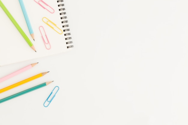 Flat lay photo of office desk with colorful pencil and paper clip, copy space top view