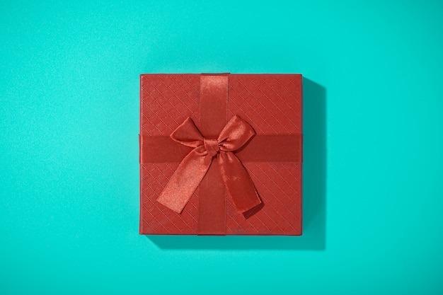 Flat lay photo of red gift box on blue table