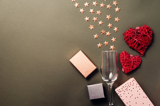 Flat lay photo of stars with glass of champagne and gift boxes with red hearts, presents for valentines day or birthday