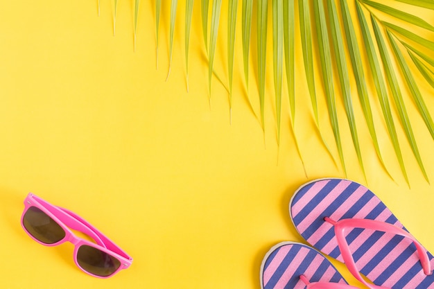 Flat lay photo sunglasses and sandals on yellow background