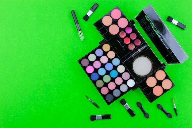 Flat lay photo of various makeup brush, eyeshadow and cosmetics